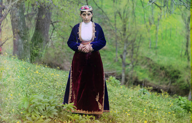 An Armenian woman in national costume poses for Prokudin-Gorskii on a hillside near Artvin (in present day Turkey), circa 1910